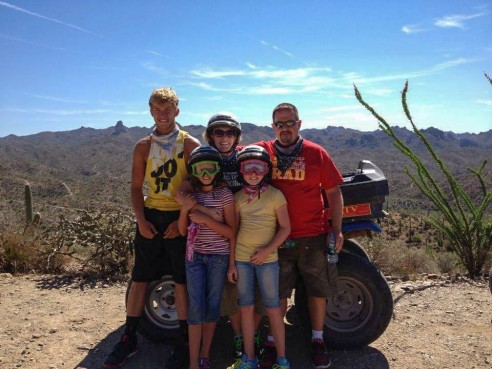 Michelle with her husband and children on an ATV ride in the desert.
